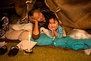 Vera Rakhtuvia, a Chukchi woman, relaxes by candlelight with her granddaughter, Susha, in the polog (sleeping area) inside the family's Yaranga (tent) at their summer camp. Iultinsky District, Chukotk...  -  Bryan and Cherry Alexander