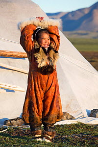 Nadia Takui, a Chukchi girl, dressed in a traditional reindeer skin Kerker (knee length coverall) outside a Yaranga (tent) at a reindeer herders' summer camp. Iultinsky District, Chukotka, Siberia, Ru...  -  Bryan and Cherry Alexander