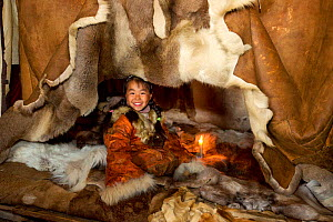 Nadia Takui, a Chukchi girl, dressed in a traditional reindeer skin Kerker, (knee length coverall) sitting at the edge of the polog (sleeping area) in a Yaranga (tent) at a reindeer herders' summer ca...  -  Bryan and Cherry Alexander