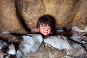 After waking up in the morning, Yaroslava Votgyrgina, a Chukchi girl, sticks her head out of the polog (sleeping area) in a Yaranga (tent) at a reindeer herders' summer camp. Iultinsky District, Chuko... - Bryan and Cherry Alexander