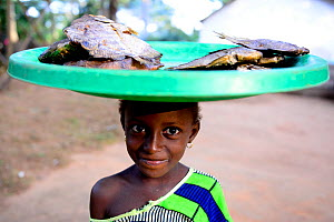 Young fish seller carrying tray on head, Iemberem village. Cantanhez National Park, Guinea-Bissau, December 2013.  -  Enrique Lopez-Tapia
