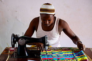 Man sewing colourful loom woven fabric at Artisan Centre, Guinea-Bissau, December 2013. - Enrique Lopez-Tapia