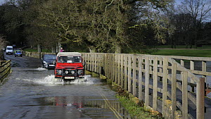 Landrover and cars driving through floods caused by the River Avon bursting its banks, Lacock, Wiltshire, England, UK, February 2014. - Nick Upton