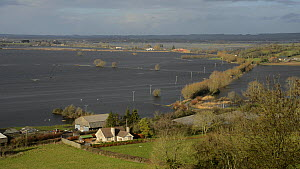 Overview of farm buildings at the edge of extensively flooded pasture land, with flooded farm tracks and road, West Sedgemoor, Somerset Levels, England, UK, February 2014. - Nick Upton
