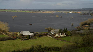 Panning shot of farm buildings at the edge of extensively flooded pasture land, with flooded farm tracks and road, West Sedgemoor, Somerset Levels, England, UK, February 2014. - Nick Upton