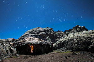 Cooking hut lit inside by a small cooking fire, with star trails, Bale Mountains National Park, Ethiopia, December 2011.  -  Will Burrard-Lucas