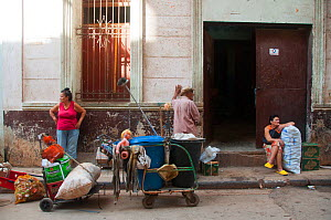 Three people on pavement including a lady leaning against wall behind bags of recycling and a wheelie bin, Havana, Cuba, October 2011.  -  RHONDA KLEVANSKY