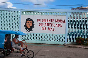 "Sign with Che Guevara and a political slogan ""Un gigante moral que crece cada dia mas""  which means ""A common sense of purpose which grows each day."" with a rickshaw passing, Baracoa, Guantanamo provi...  -  RHONDA KLEVANSKY"
