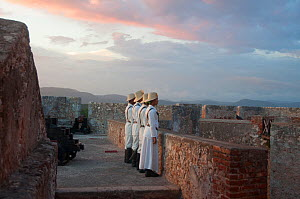 Four people in traditional costumes lined up against wall, part of a Canon lighting ceremony at sunset, Fort, Santiago de Cuba, Cuba, November 2011.  -  Rhonda Klevansky