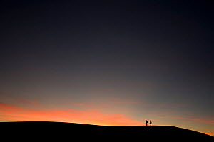 Two people silhouetted on sand dune ridge at sunset, White Sands National Park, New Mexico, USA, December 2012.  -  Peter Cairns