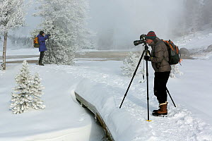 Two photographers on path, Upper Geyser Basin, Yellowstone National Park, Wyoming, USA, February 2014.  -  Kirkendall-Spring