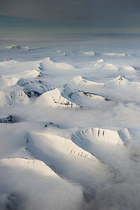 Aerial view of the mountains of southern Spitsbergen covered in snow with low clouds, Svalbard, Norway, June 2013.  -  Roy Mangersnes