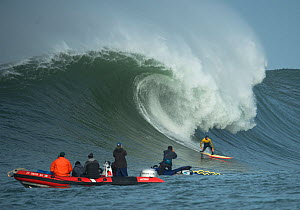 Surfer competing in the Mavericks 2014 surfing competition, watched by people on RIB, Half Moon Bay, California, USA, January 2014.  -  Michael  D. Kern