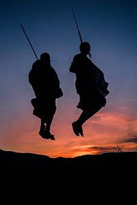 Two Masaai warriors silhouetted performing traditional jump / leap kopje at sunset. Ngorongoro Conservation Area / Serengeti National Park, Tanzania. March 2014.  -  Nick Garbutt
