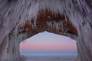 Icicles hanging from sandstone archway in sea cave at dawn. Apostle Islands National Lakeshore, Lake Superior, Squaw Bay, Wisconsin, February 2014. Exposure composite of 3 images.  -  Thomas Lazar