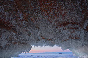 Icicles hanging from sandstone ceiling of sea cave on frozen lake. Apostle Islands National Lakeshore, Lake Superior, Squaw Bay, Wisconsin, January 2014. Exposure composite of 3 images.  -  Thomas Lazar