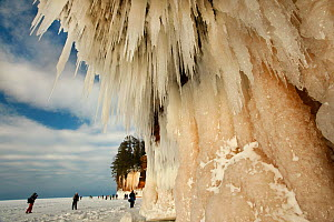Hikers on frozen lake looking at sea caves and ice formations, Apostle Islands National Lakeshore, Lake Superior, Squaw Bay, Wisconsin, February 2014.  -  Thomas Lazar