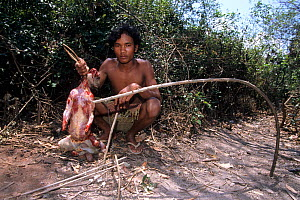 Man with Crab-eating macaque (Macaca fascicularis) caught in trap, dead and skinned, Cambodia.  -  Roland  Seitre
