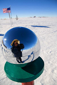 Self portrait of photographer Cherry Alexander in the reflection of the metallic sphere at the ceremonial South Pole, Antarctica.  -  Bryan and Cherry Alexander