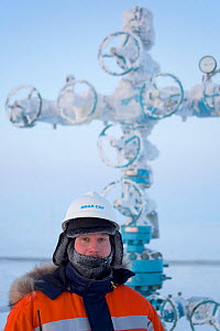 Evgeniy Petrov, a safety officer for Yamal SPG, stands infront of a 'Christmas tree' (valve assembly) at a drilling site in the South Tambey Gas Field, Yamal Peninsula, Siberia, Russia. February 2014.  -  Bryan and Cherry Alexander