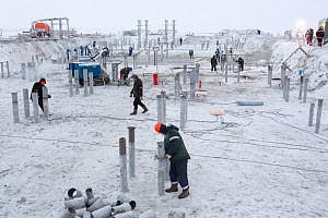 Workers wearing protective winter clothing against the cold at a construction site near Sabetta in the South Tambey Gas Field, Yamal Peninsula, Siberia, Russia. February 2014. - Bryan and Cherry Alexander