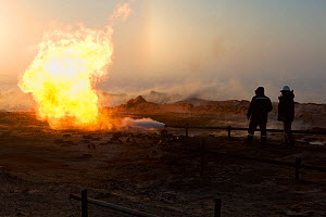 Two gas field workers standing near a flare at a drilling site in the South Tambey Gas Field, Yamal Peninsula, Siberia, Russia. February 2014.  -  Bryan and Cherry Alexander