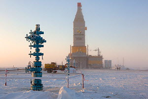 A gas drilling derrick in the distance behind a 'Christmas tree' (valve assembly), South Tambey Gas Field, Yamal Peninsula, Siberia, Russia. February 2014.  -  Bryan and Cherry Alexander