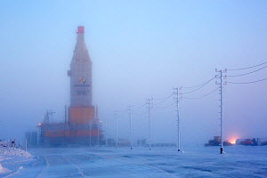 Fog surrounding a gas drilling derrick at dusk, near the South Tambey Gas Field, Yamal Peninsula, Siberia, Russia. February 2014.  -  Bryan and Cherry Alexander