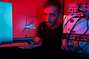 Dr. Uwe Homberg, taking notes and observing experimental set-up to investigate the orientation behaviour of Desert locusts (Schistocerca gregaria). The grasshopper is fixed and placed behind a fan. Th... - Ingo Arndt