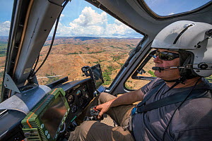 Food and Agriculture Organization (FAO) helicopter pilot Eric Gadot, an expert at locust control operations flying over effected area, near Miandrivazo, Madagascar. December 2013.  -  Ingo Arndt