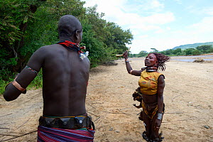 During the Ukuli ceremony and before the bull jumping, the Maza (young initiated men) whip the Hamer women who will defy them, showing no fear or signs of pain. Hamer tribe, Omo river Valley, Ethiopia...  -  Eric Baccega