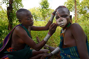 Young Suri / Surma woman painting another woman's face. Omo river Valley, Ethiopia, September 2014.  -  Eric Baccega