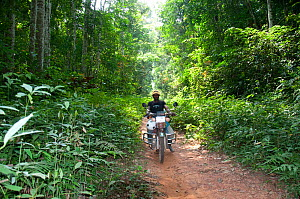 Man riding motorbike through the Ituri Rainforest, Democratic Republic of the Congo, Africa, December 2011. - Steve O. Taylor (GHF)