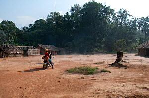 Mbuti Pygmy village, with non-pygmy man on motorbike, Democratic Republic of the Congo, Africa, January 2012. - Steve O. Taylor (GHF)