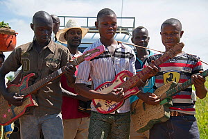 Men in village playing on home made four string guitars on road to Katanga, Democratic Republic of Congo, March 2012. - Steve O. Taylor (GHF)