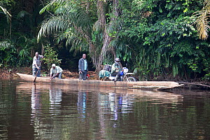 Local people crossing river in wooden dugout canoe, including man with goods on motorbike, Salonga National Park, Equateur, Democratic Republic of the Congo, May 2012.  -  Steve O. Taylor (GHF)