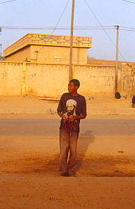 Young man waiting for taxi wearing Osama bin Laden t shirt, Niger, 2003.  -  Steve O. Taylor (GHF)