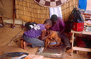 Leather traders repairing bag. Niamey, Niger, 2004. - Steve O. Taylor (GHF)