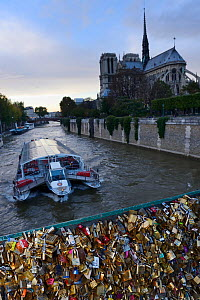 Padlocks on the Pont de l'Archeveche bridge and Notre Dame Cathedral, with boat passing, Paris, France, October 2013. - Staffan Widstrand