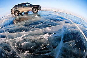 Wide angle view of vehicle parked on ice on lake surface. Lake Baikal, Siberia, Russia, March 2007.  -  Olga Kamenskaya