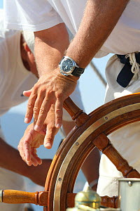 Crew member at the helm of the 1911 Classic yacht Mariquita, St. Tropez, France, September 2013. All non-editorial uses must be cleared individually. - Ingrid  Abery
