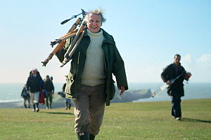 David Attenborough carrying tripod back from a shoot on the Worm's Heads, on production for The Trials of Life. Gower Peninsula, Wales, UK, 1988. Small reproduction only. - Nick Upton