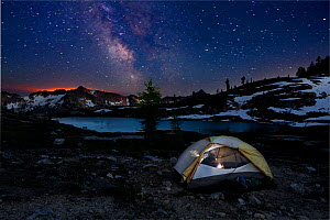 Campsite at night in Snowy Lakes Basin, glow of forest fire on the horizon. North Cascades area of the Okanogan Wenatchee National Forest, Washington, USA, July 2014. Model released.  -  Kirkendall-Spring