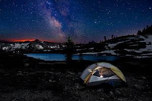 Camper inside tent reading  at night in  Snowy Lakes Basin, glow of forest fire on the horizon. North Cascades area of the Okanogan Wenatchee National Forest, Washington, USA, July 2014. Model release...  -  Kirkendall-Spring