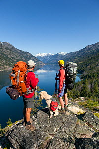 Backpackers with dog looking out over lake on the Lake Chelan Trail between Moore Point and Stehekin, Lake Chelan-Sawtooth Wilderness, Washington, USA, May 2014. Model released. - Kirkendall-Spring