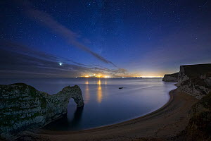 Stars and Milky Way over Durdle Door and the Jurassic Coast, with the lights of Weymouth and Portland beyond, Dorset, England, UK, December 2013.  -  David Noton