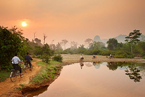 Children riding bikes along riverside path at dawn, near Vang Vieng, Laos, March 2009.  -  David Noton