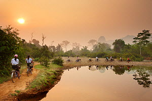 Cyclists riding bikes along riverside path at dawn, near Vang Vieng, Laos, March 2009. - David Noton