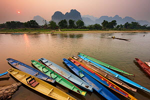 Canoes on the moored on the  Nam Song River at Vang Vieng, Laos, March 2009. - David Noton