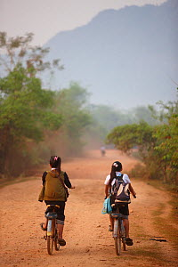 Children cycling to school, near Vang Vieng, Laos, March 2009.  -  David Noton